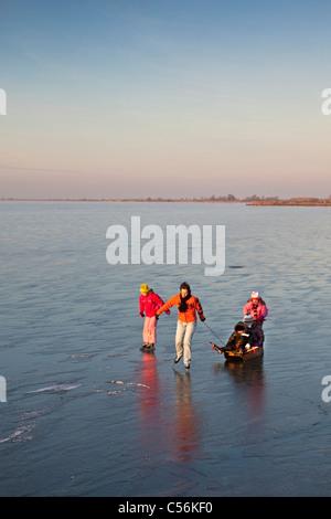 Die Niederlande, Marken, Mutter mit Kindern und Rodeln Eislaufen auf dem zugefrorenen See IJsselmeer genannt. - Stockfoto