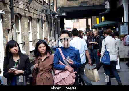 Modische jungen Asiaten auf der Brick Lane im East End von London. VEREINIGTES KÖNIGREICH. - Stockfoto