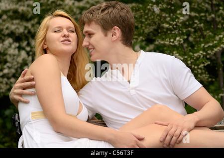 Liebespaar berühren und talking beim Faulenzen auf einer Bank in einem Park mit Blüten - Stockfoto