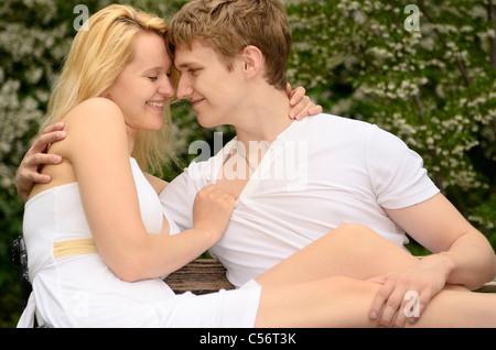 Paar berühren und lächelnd, während auf einer Bank in einem Park mit Blüten im Frühjahr High Park Toronto - Stockfoto