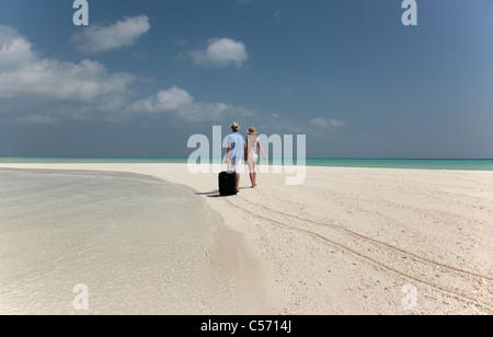 Paar rollende Gepäck am Strand - Stockfoto
