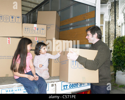 Familie Auspacken Boxen von Umzugswagen - Stockfoto