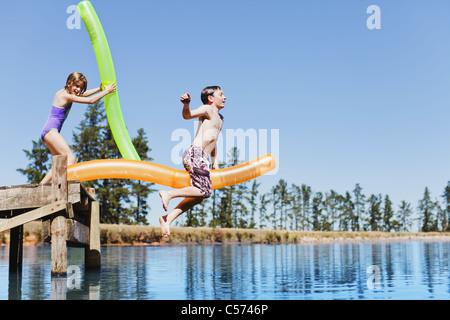 Kinder springen von der Anlegestelle in See - Stockfoto