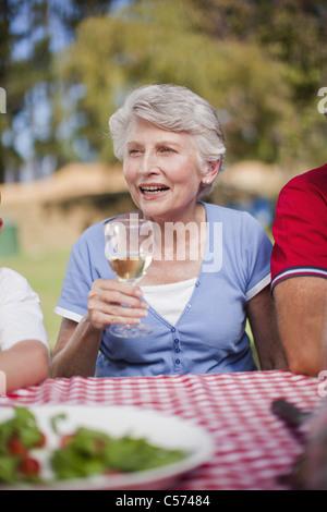 Ältere Frau trinkt am Picknicktisch - Stockfoto