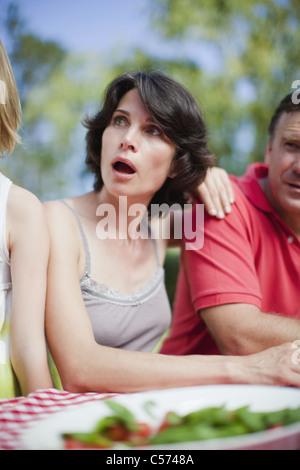 Überrascht Frau sitzt an Picknick-Tisch - Stockfoto