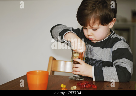 Junge mit Süßigkeiten am Tisch spielen - Stockfoto