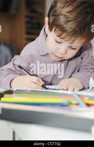 Junge mit Farbstiften zeichnen Stockfoto