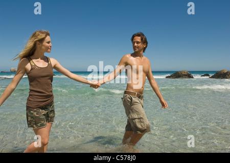Paare, die Hand in Hand am Strand - Stockfoto