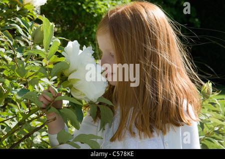 Mädchen Blumen im Garten riechen - Stockfoto