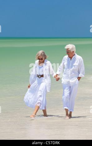 Glückliches Paar der senior Mann und Frau gehen, Lächeln auf den Lippen und Hand in Hand auf einem einsamen tropischen - Stockfoto