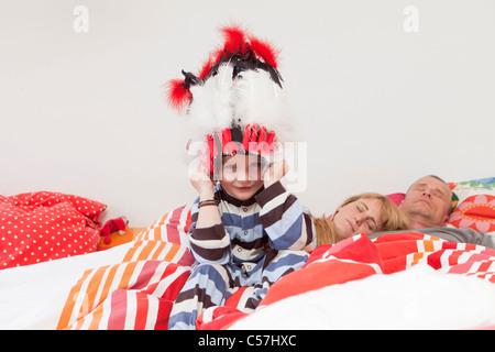 Jungen tragen Krieg Motorhaube im Bett der Eltern - Stockfoto