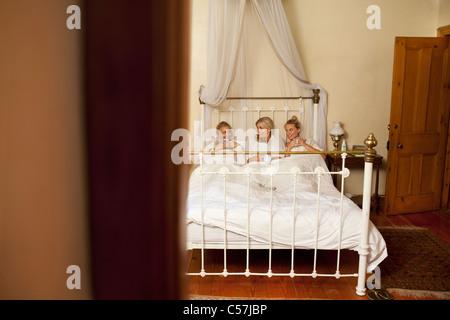 Mutter und Töchter mit Kaffee im Bett - Stockfoto