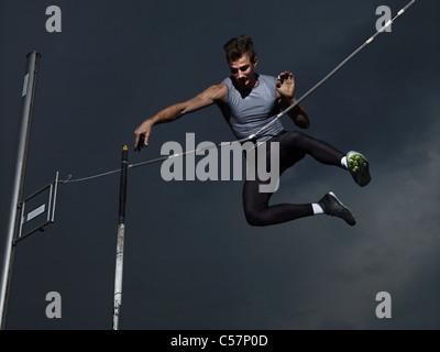 Mann springt Luft im Stabhochsprung - Stockfoto