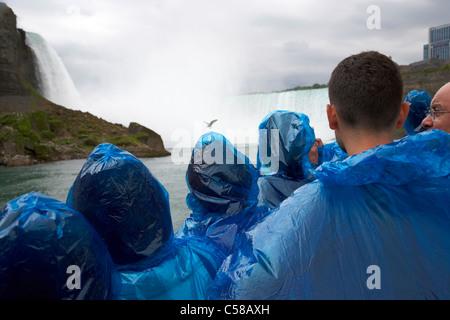 Touristen in blauem Kunststoff wasserdicht Ponchos Annäherung an den Horseshoe Falls auf Mädchen des Nebels Niagara - Stockfoto