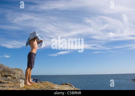 Mann nach einem Schwimmen stehen auf Felsen ruhige Meer - Stockfoto
