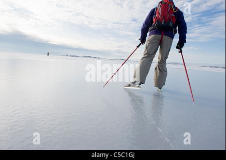 Ansicht von hinten ein Mann Eislaufen gegen bewölktem Himmel - Stockfoto