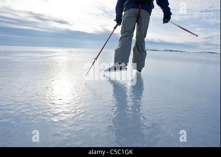 Hinteren Ansicht niedrigen Bereich ein Mann Eislaufen gegen bewölktem Himmel - Stockfoto