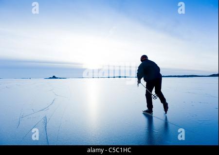 Ansicht von hinten ein Mann Eislaufen gegen klaren Himmel - Stockfoto