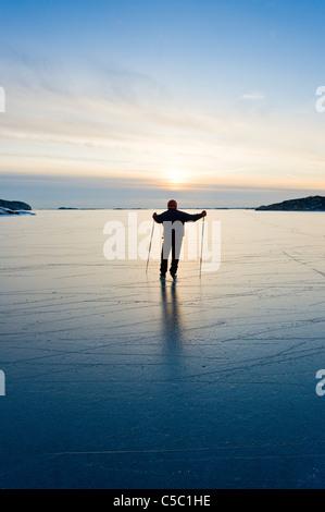 Rückansicht einer Silhouette Mann Eislaufen gegen den Himmel in der Abenddämmerung - Stockfoto