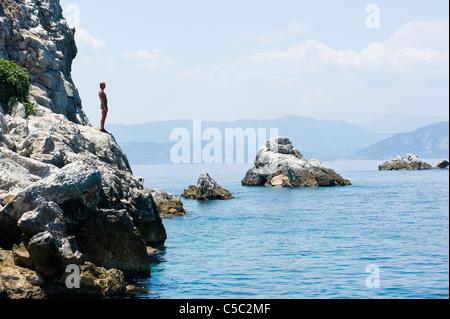 Seitenansicht eines Mannes auf einer Klippe am ruhigen Meer - Stockfoto