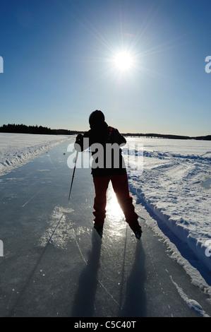 Rückansicht des eine Silhouette Mann Eislaufen bei Sonnenschein im Hintergrund - Stockfoto