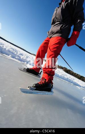 Niedrige Abschnitt eines Mannes Schlittschuhlaufen auf zugefrorenen See gegen klar blauen Himmel - Stockfoto