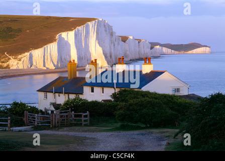 Ein Abend-Blick in der Nähe von Sonnenuntergang der sieben Schwestern und Coastguard Cottages von Seaford Kopf, - Stockfoto
