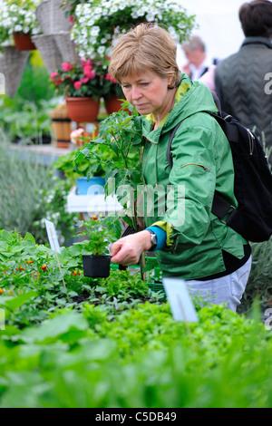 Seitenansicht der eine Frau mittleren Alters mit Rucksack auf dem Blumenmarkt - Stockfoto