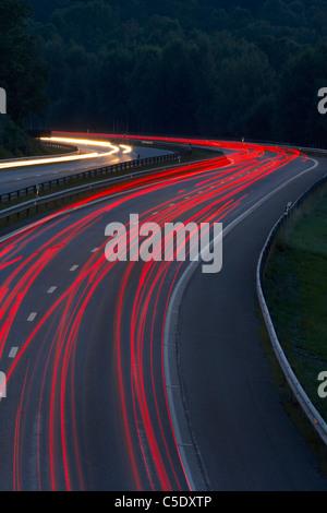 Roten unscharfen Lichtspuren von Fortbewegungsmitteln auf Asphaltstraße - Stockfoto