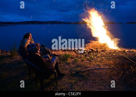 Leute sitzen am Lagerfeuer von friedlichen See am Walpurgisnacht in Schweden - Stockfoto
