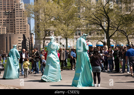 Touristen, posiert mit Statue von Liberty Street Artists, Battery Park, New York City - Stockfoto