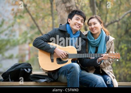 Ein junger Mann spielt Gitarre wie He Freundin lehnt sich an ihn liebevoll - Stockfoto