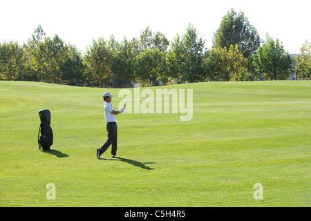 Junger Mann, die Einnahme eines Golfschwungs - Stockfoto