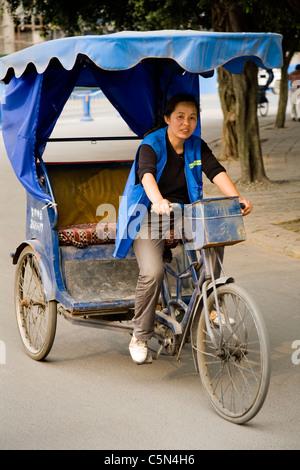 Trishaw/tri-Shaw/Zyklus Rikscha und Frau/Frau Radfahrer/Treiber in Leshan Stadt, Provinz Sichuan. China. - Stockfoto