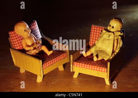 Zwei kleine alte Puppen im Sessel sitzen. - Stockfoto
