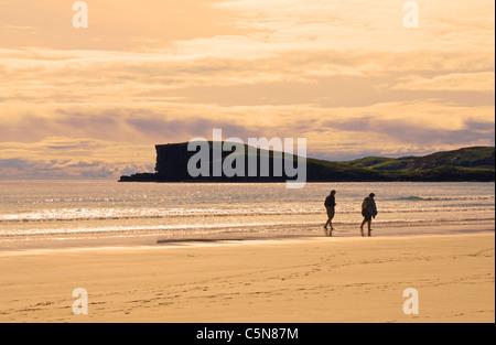 Ein paar schlendert barfuß entlang des Wassers bei oldshoremore Strand, abends, in der Nähe von Kinlochbervie, Sutherland, - Stockfoto