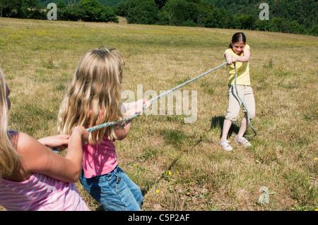 Drei Mädchen spielen Tauziehen im Feld - Stockfoto