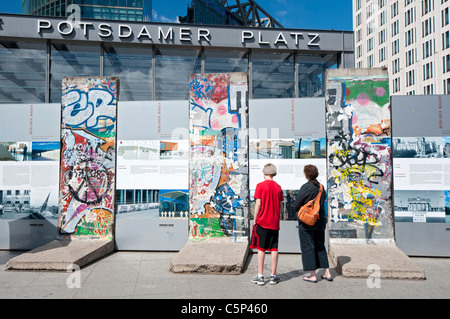 Touristen, die gerne am ursprünglichen Teile der Berliner Mauer am Potsdamer Platz in Berlin-Deutschland - Stockfoto