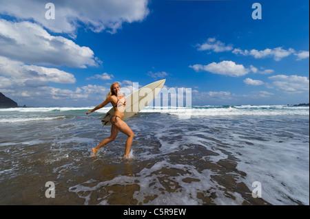 Ein junger Surfer läuft durch das Meer. - Stockfoto