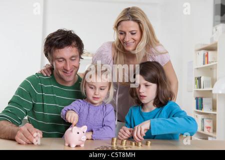 Deutschland, Bayern, München, Familie mit Münzen und Sparschwein, Lächeln - Stockfoto