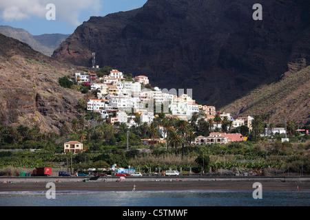 Spanien, Kanarische Inseln, La Gomera, Valle Gran Rey, La Calera, Touristen am Strand mit Bergen - Stockfoto
