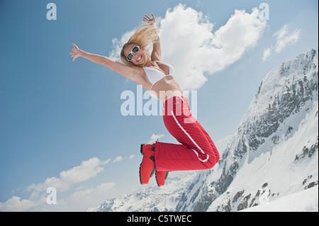 Österreich, Salzburger Land, junge Frau in die Luft springen - Stockfoto