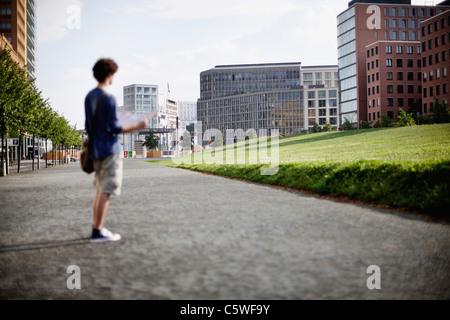 Deutschland, Berlin, junger Mann mit Stadtplan - Stockfoto
