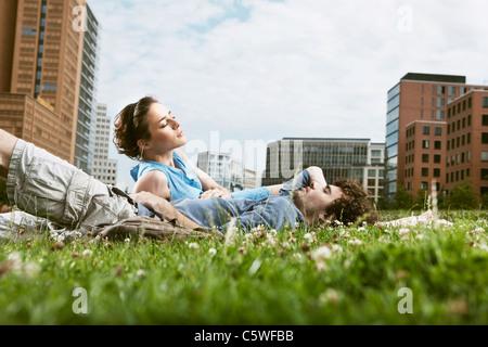 Deutschland, Berlin, junges Paar liegen auf Wiese, Hochhäuser im Hintergrund