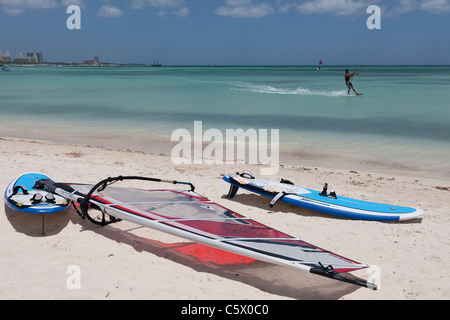 Surfbretter auf Palm Beach, Aruba, Niederländische Karibik mit einem Kitesurfer im Hintergrund - Stockfoto