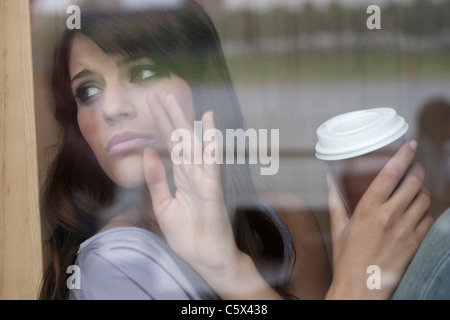 Deutschland, Köln, junge Frau sitzt im Fenster des café - Stockfoto