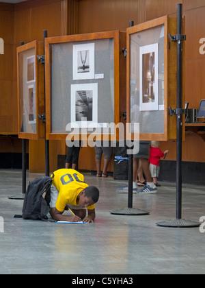 Schüler schreiben auf Boden in Brooklyn Public Library - Stockfoto