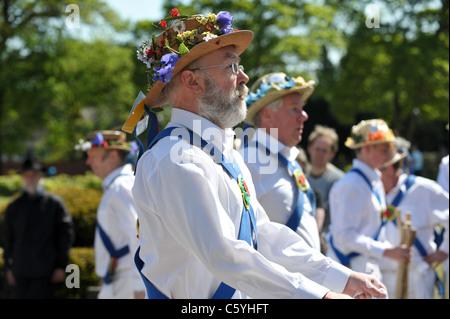 Eine Gruppe von traditionellen englischen Morris Tänzer tragen weiße Hemden und Strohhüte bedeckt Frühlingsblumen - Stockfoto