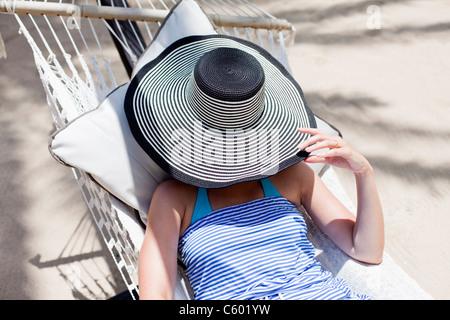 Eine Frau für ihr Gesicht mit einem Schlapphut in einer Hängematte in Antigua - Stockfoto
