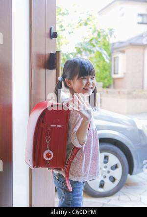 Mädchen vor der Tür Hand winken - Stockfoto